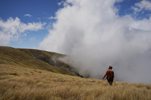 a woman walking through a field of tall grasses on a mountaintop in the clouds