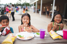 children eating hamburgers at a picnic table