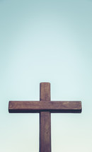 Empty wooden cross against a blue sky