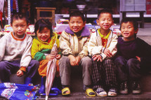 young kids sitting on a curb