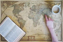 a woman pointing to a world map