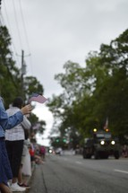 Army trucks and American flags at a parade