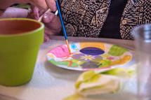 Painting a terracotta pot.