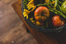 basket of tomatoes, green beans, and sunflowers