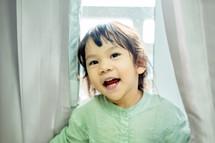 a little girl standing at a window