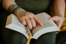 person with tattoos reading a Bible