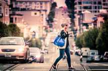 woman with a purse crossing a busy street