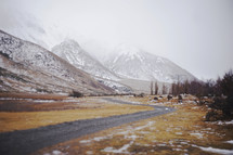gravel road and snow capped mountains