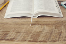 coffee cup, pencil, open Bible, and cellphone on a desk