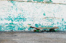 Skateboard on the pavement by a weathered wall.