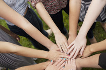 A group of girls bond as they put their hands together.