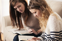 Friends reading Bibles together on a couch.