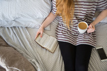 girl sitting on a bed with coffee reading a Bible