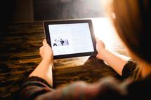 a woman reading off an iPad screen
