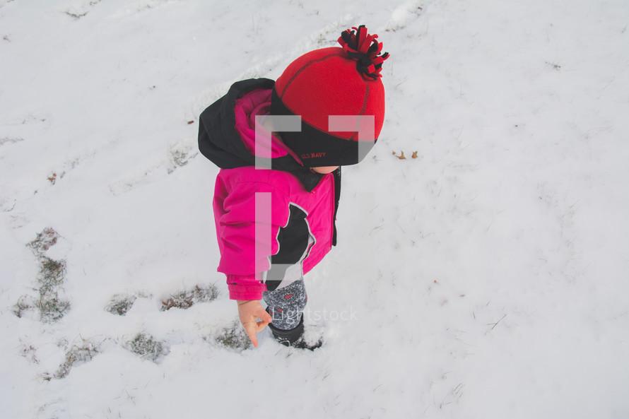 A toddler walking in snow