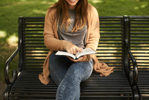 a woman sitting on a park bench reading a Bible in fall