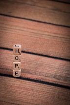 "A stack of dice, spelling ""hope,"" on a wooden table."