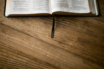 edge of an open Bible lying on a wood table
