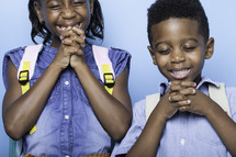 children praying before the first day of school with book bags