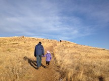 a father and daughter walking up a hill holding hands