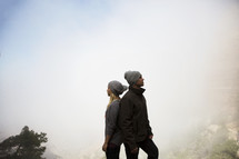 couple standing on a foggy mountaintop back to back