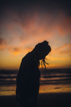 silhouette of a woman looking down standing on a beach at sunset