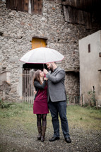 a couple looking into each other's eyes under a umbrella