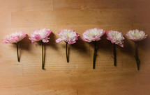 A row of pink flowers on a wooden table.