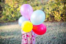 child holding helium balloons