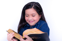 Smiling girl reading the Bible.