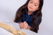 Girl reading an open Bible.