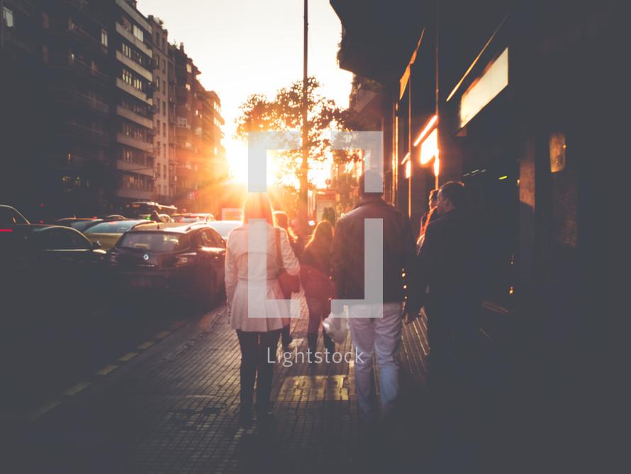 people walking on a sidewalk and intense sunlight