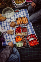 people sitting on a picnic blanket with various snack foods