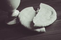 A wine cup and broken bread on a wooden table.