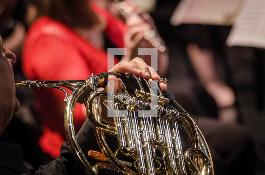 man playing a French horn