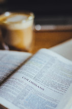 A coffee and bible open to Colossians