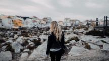 blonde woman in a coat walking on a beach