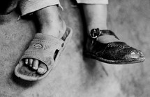 Child wearing different shoes on each foot