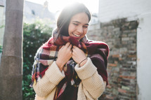 a woman wrapped in a plaid shaw