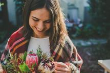a woman enjoying a bouquet of flowers