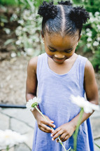 An African American girl holding a spring flowers