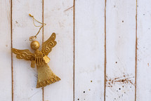 gold angel ornament on white boards