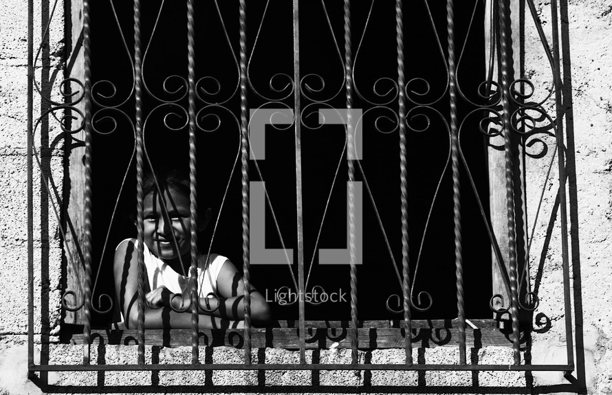 A girl smiling from behind a window with bars