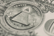 Closeup of the back of a dollar bill showing the Pyramid, eye emblem