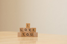 """I love you"" spelled out in stacked scrabble tiles"