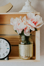 flowers in a vase on a shelf