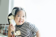 a toddler girl talking on an antique phone