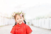 a little girl in a red traditional Chinese dress