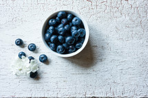 a bowl of blueberries on wood