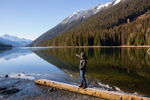 a man standing on a lake shore in Canada